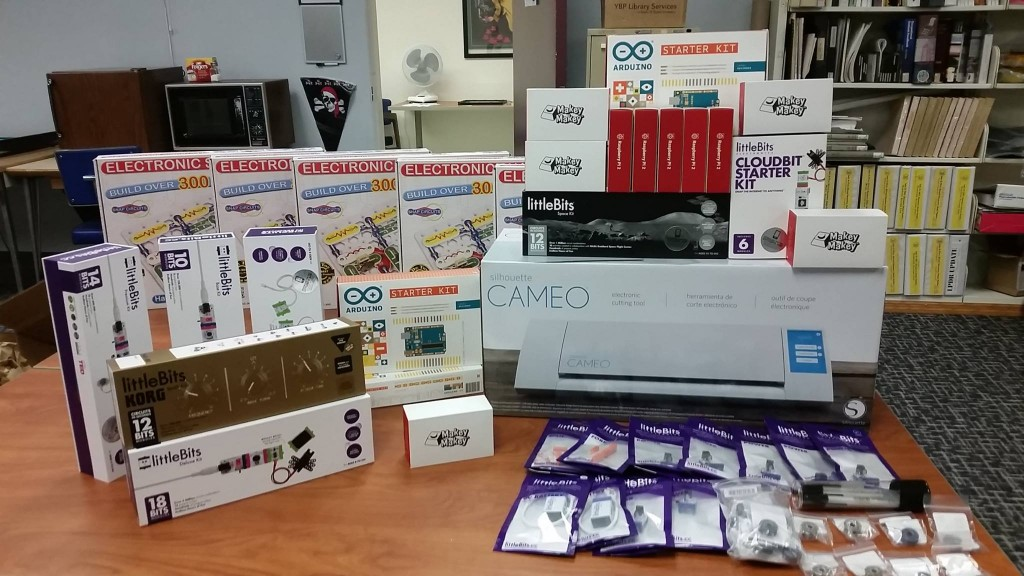 A pile of boxes and packages on a table, including items such as a Silhouette Cameo, littleBits, Makey Makeys, and Arduinos.