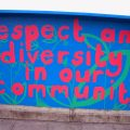 "wall painted with the words ""respect and diversity in our community"""