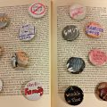 Buttons arranged on an open book with designs such as book covers and slogans in favor of banned books and against censorship.