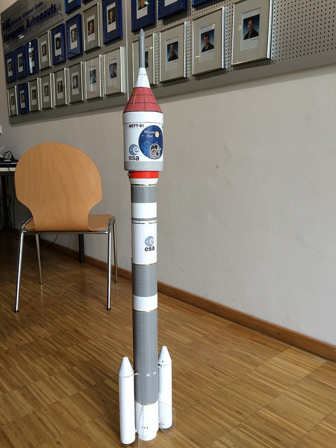 A sturdy model rocket sitting on its end.