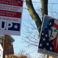 """Protest signs being held in the air. One reads: Immigrants make America great, Build bridges not walls, Love Trumps Hate, UP. The other depicts a Muslim woman with an American flag-style head covering and reads """"We the people are greater than fear"""""""