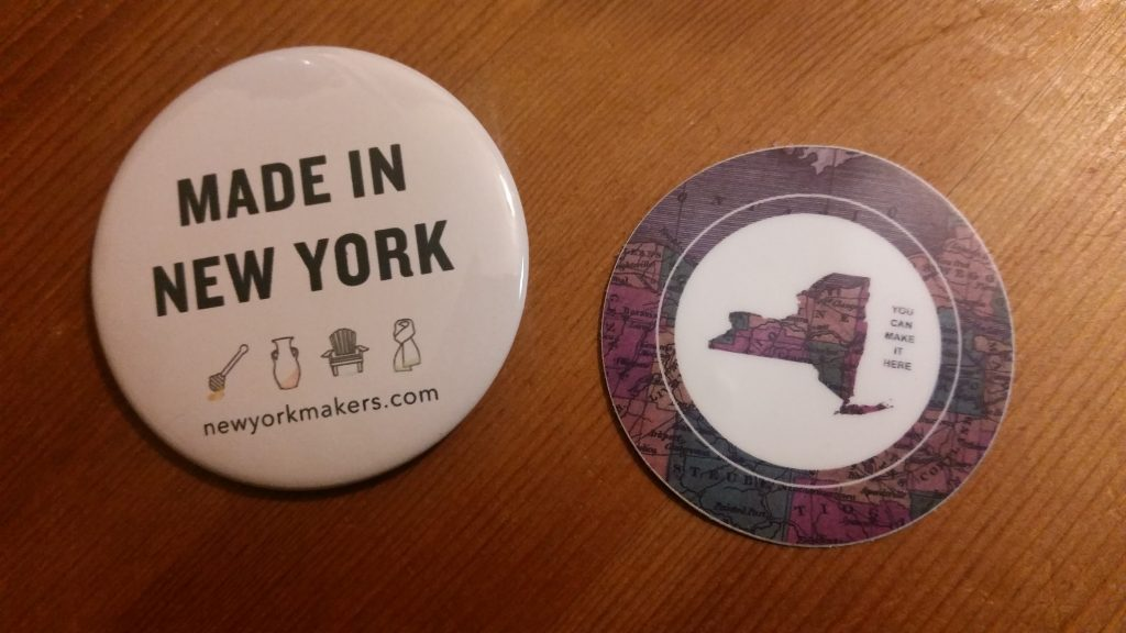 Button that reads Made in New York next to a sticker with a picture of New York State and the words You Can Make It Here