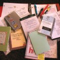 Notebooks of varying types and sizes scattered in a messy pile on a desk.