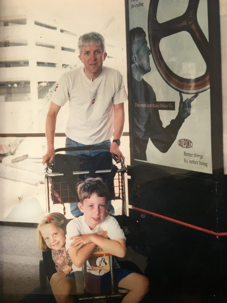 Mark Hopkins standing with his two young children in front of an advertisement featuring his image and a unique bike wheel.