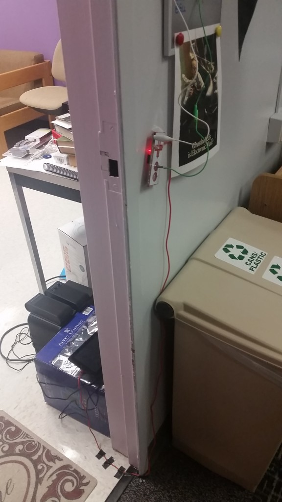 The setup of the doorbell, with the Raspberry Pi and speakers just visible on one side of the wall through the doorway. The other side of the wall has the Makey Makey attached to it with the alligator clips coming off it.