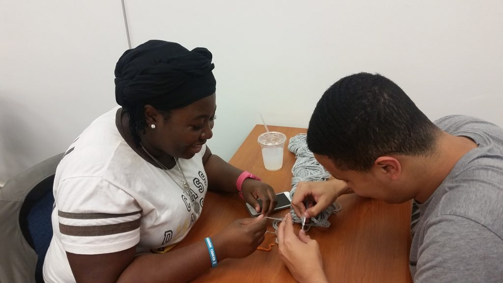 A young woman and young man working together with crochet hooks and yarn