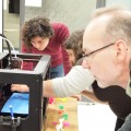 Three people gathered around a 3D printer. One person is pointing and demonstrating.