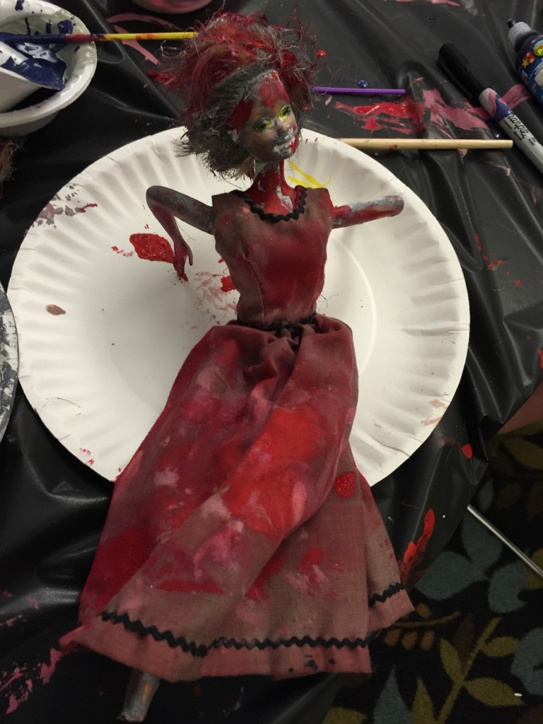 Barbie doll sitting on a paper plate with red and black painted skin, hair, and dress.