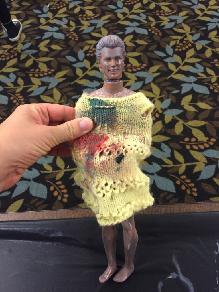 Ken doll with grey skin wearing a long sweater stained with paint.